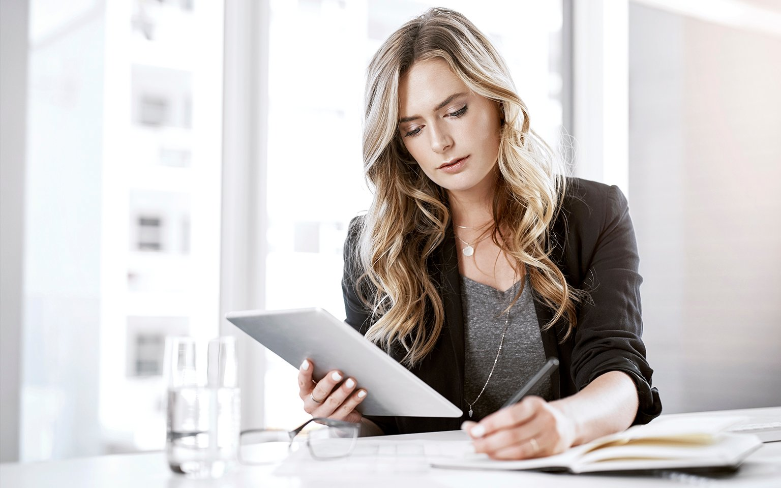 woman writing while looking at the tablet